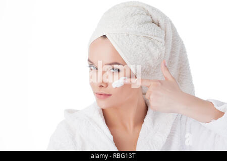 To use the cream after a shower. Portrait of a young attractive woman in a Bathrobe and a towel on her head. girl uses a cream and face mask. - Stock Photo