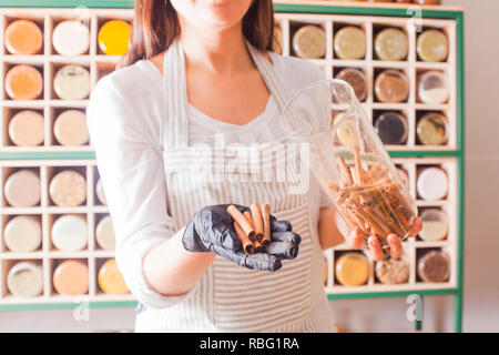 Straight rows of glasses with various grinned herbs in the grocery shop. Woman shows the cinnamon sticks for the customer - Stock Photo