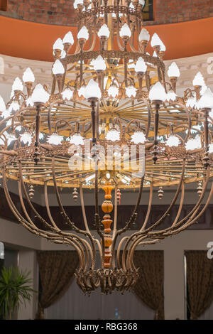 Huge chandelier in the hall. Chandelier on decoarted ceiling of a ballroom. vertical photo - Stock Photo
