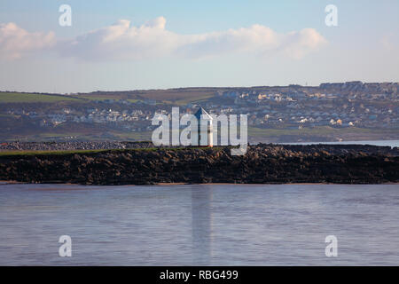 The landmark white Lighthouse atop the rocky outcrop at sand bay and trecco bay adjacent to Porthcawl viewed across the bay from the promenade. - Stock Photo