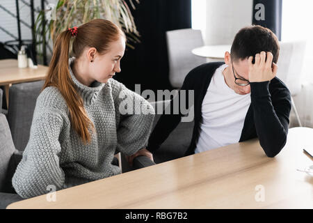 Unhappy young couple arguing, angry wife looking at husband blaming him of problems, conflicts in marriage, bad relationships, man and woman having quarrel or disagreement - Stock Photo