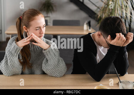Bad relationship concept. Man and woman in disagreement. Young couple after quarrel sitting next to each other. Outdoor - Stock Photo