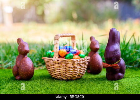 Chocolate Easter bunny with straw basket full of colourful eggs on green grass background - Stock Photo