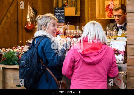 Man working at stall selling alcoholic fruit liqueurs & potential customers (women pals) enjoying sample drinks - York Christmas Market, England, UK. - Stock Photo