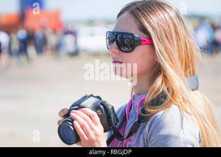 Unfamiliar girl in sunglasses with a camera - Stock Photo