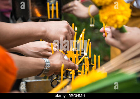 People light candles in a Buddhist temple in Thailand - Stock Photo