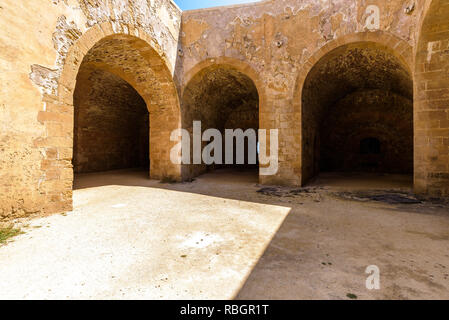 Stone roman arches linking rooms inside the Maniace Castle in the island of Ortigia, built during the Swabian period by Emperor Frederick II of Swabia - Stock Photo