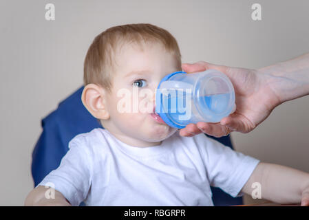 Little baby boy drinking water while sitting on a chair in the kitchen. Mother holding out a plastic bottle in her hand - Stock Photo