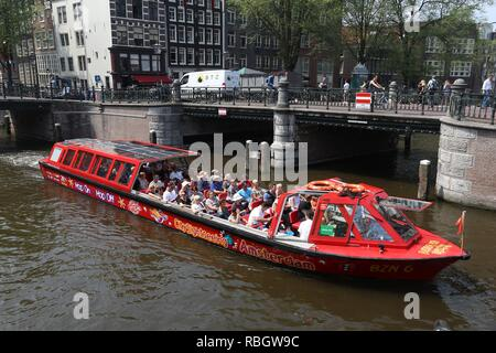 AMSTERDAM, NETHERLANDS - JULY 7, 2017: People ride tour boat at Prinsengracht and Leidsegracht canal intersection in Amsterdam, Netherlands. - Stock Photo