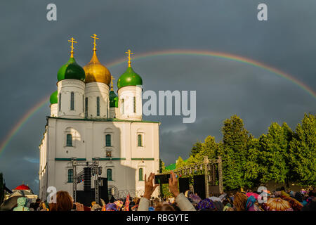 Rainbow over the snow-white temple in the dramatic sky. Cathedral Square of the city of Kolomna of the Moscow region. People take pictures of a rainbo - Stock Photo