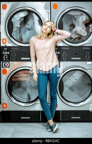 Young woman with boring emotions standing near the dryer machines waiting for clothes to be dried in the laundry - Stock Photo