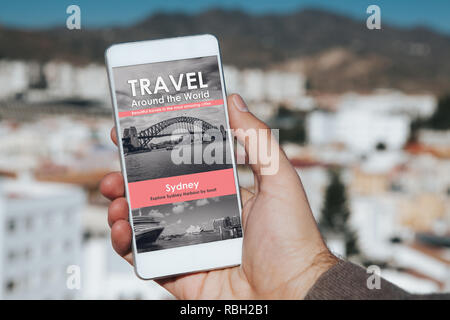 Man holding a mobile phone in the hand with travel agency website in the screen, with city background. - Stock Photo