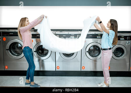 Young women throwing up a bedsheet making clothes after the washing in the public laundry