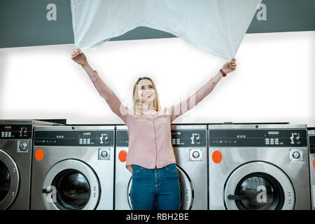Young woman throwing up a bedsheet making clothes after the washing in the public laundry