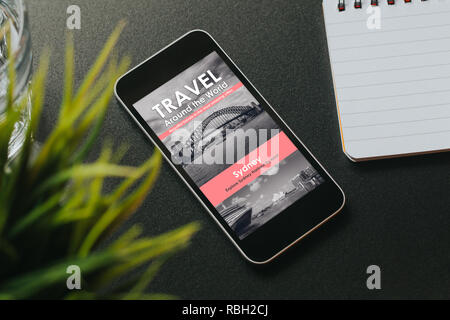 Travel agency website in a mobile phone screen placed over a black desk. - Stock Photo