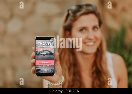 Cute blonde woman holding a mobile phone in the hand with travel agency website in the screen. - Stock Photo