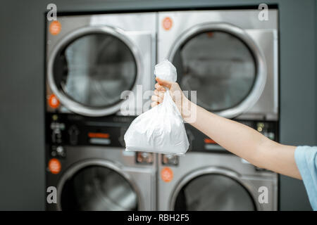 Holding bag with white washing powder with professional machines on the background at the laundry