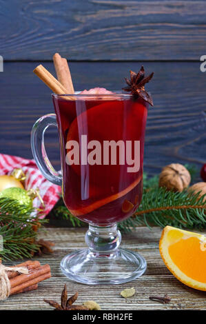 Hot mulled wine in glass mug on a wooden table. Fragrant traditional winter drink based on wine, juice, spices, seasonings, fruits. Close up - Stock Photo