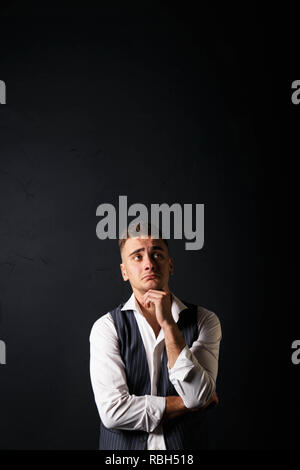 Portrait of young handsome man wearing white shirt standing on the gray background and showing sad face - Stock Photo