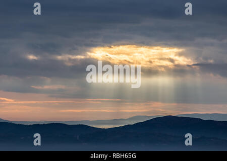 Sunray shines through clouds over the mountains and a sea of fog - Stock Photo