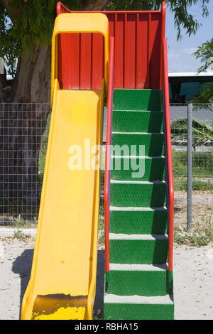 Closeup of Yellow Slide alongside the Green Steps Facing Front on Sunny Day. Playground Secluded with Iron Screen Fence. Recreational Activity for Chi - Stock Photo