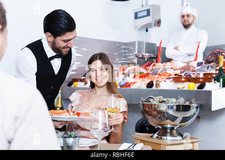 Polite smiling young waiter bringing ordered seafood dishes to smiling couple at fish restaurant - Stock Photo