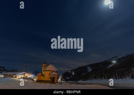 Night view of a small church at the San Pellegrino Pass in winter, with the snow-covered ski slopes in the background, Dolomites, Italy - Stock Photo
