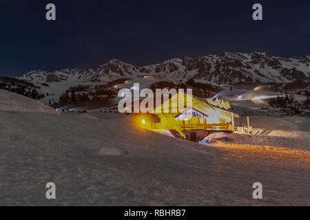 Illuminated chalet in the evening with snow cannons on the background preparing the ski slopes, Passo San Pellegrino, Dolomites, Italy - Stock Photo