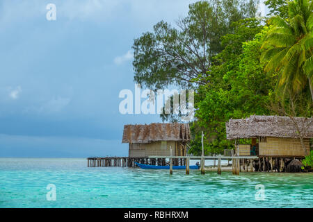 The shore of a small island in Indonesia. Two straw bungalows on stilts. Lush tropical vegetation - Stock Photo