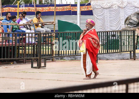 Temple priest at Mysore Dussehra celebration or Dasara festival procession at the Mysore palace of Indian Maharaja or king in Karnataka India - Stock Photo