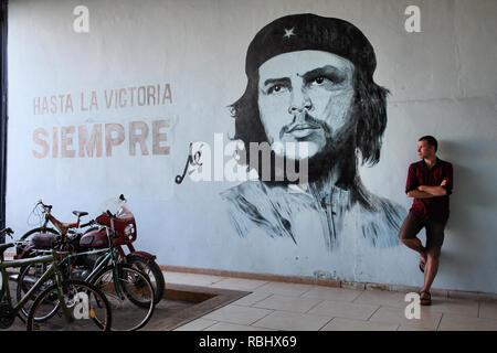 SANTA CLARA, CUBA - FEBRUARY 22: Tourist stands next to wall mural with revolution propaganda on February 22, 2011 in Sancti Spiritus, Cuba. Revolutio - Stock Photo