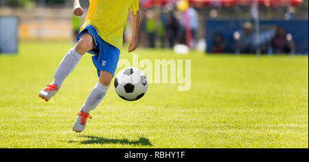 Young Soccer Player Kicking Ball. Horizontal Football Match Image with Blurred Pitch in the Background - Stock Photo