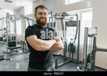 Smiling positive confident male personal instructor with arms crossed in fitness gym. - Stock Photo
