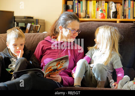 A mum sat on a sofa reading a book to her two young children - Stock Photo