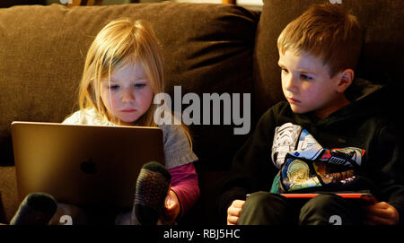 A little girl (4 yrs old) sat on a sofa using a laptop computer while her brother (6 yrs old) watches. - Stock Photo