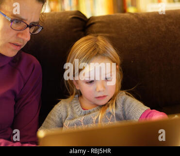 A little girl (4 yrs old) and her mum sat on a sofa using a laptop computer together - Stock Photo