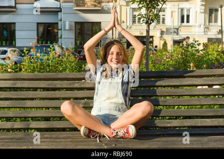the girl in a pose of a relaxation sits on a sandy beach