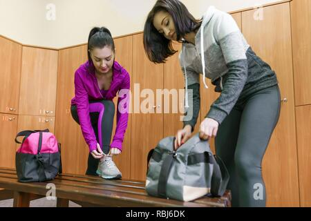 Two young fitness women in dressing room at the gym. Fitness, sport, training, people, healthy lifestyle concept - Stock Photo