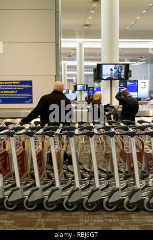 People standing by rows of luggage trolleys in Toronto Pearson airport waiting for their luggage to arrive. - Stock Photo