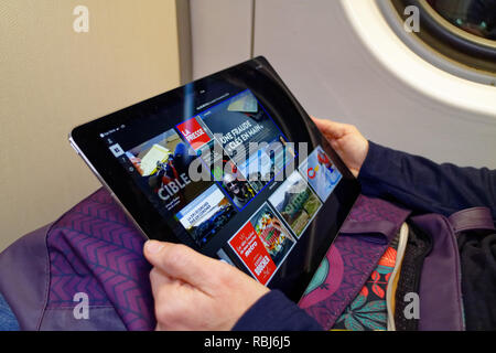 A woman's hands holding a new 12.9 inch iPad Pro and reading her Quebecois newspaper on it. - Stock Photo