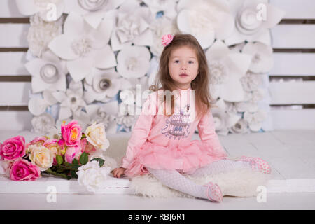 Pretty girl with brunnete hair stylish dressed in pink dress pinky skirt shirt happyly smiling posing to camera for photosession in modern showroom st - Stock Photo