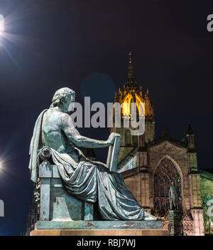 David Hume statue by Alexander Stoddart lit at night with St Giles Cathedral, Royal Mile, Edinburgh, Scotland, UK - Stock Photo