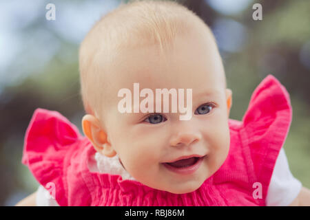 Portrait of Cute baby blond girl child wearing red jeans dress happyly smiling on camera summer time joy. - Stock Photo