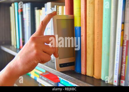 Electronic book picked from a library shelf. The electronic book on a bookshelf among the many books in the library. Booksand library concept - Stock Photo