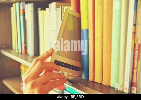 Electronic book picked from a library shelf. The electronic book on a bookshelf among the many books in the library - Stock Photo