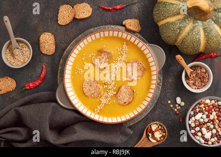 Pumpkin and mixed beanscreme soup in ceramic bowl, top view with ingredients and spices, top view on dark background