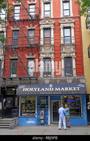 Two men outside Holyland Market, 122 St Marks Place, East Village, New York, NYC, NY, USA - Stock Photo