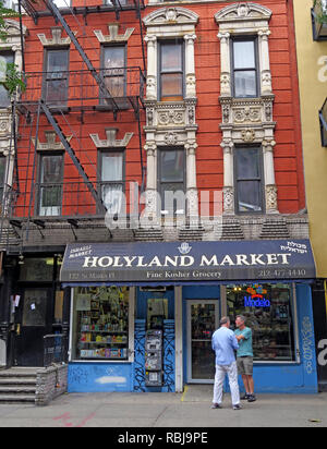 Two men outside Holyland Market, 122 St Marks Place, East Village, New York, NYC, NY, USA - Stock Photo