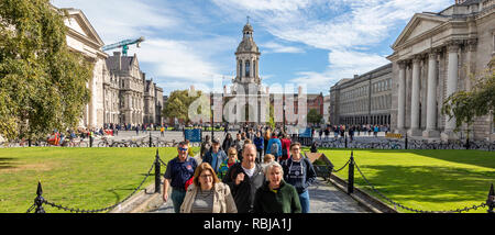 Tourists and visitors walking the grounds of Trinity Colllege in Dublin, Ireland. - Stock Photo