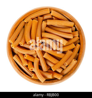 Chickpea pasta in wooden bowl. Brown Sedanini Rigati. Uncooked dried glutenfree noodles made from Cicer arietinum flour. Short length tubes. - Stock Photo
